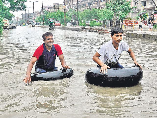 Residents use inflated tubes to commute through a waterlogged street in Shalimar Garden, Ghaziabad, on Saturday. (Sakib Ali/HT Photo)
