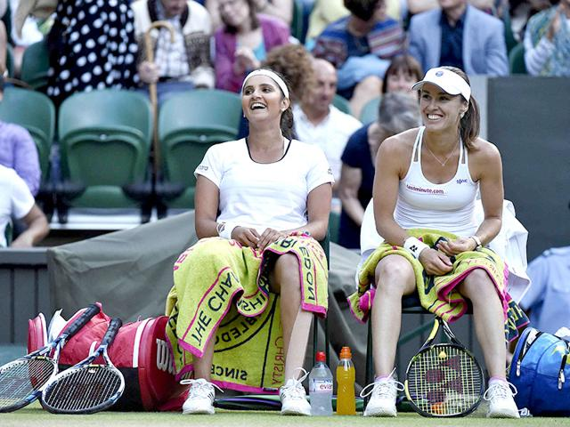Elena Vesnina, left, and Ekaterina Makarova of Russia high five during the women's doubles final of the 2015 Wimbledon Championships against Martina Hingis of Switzerland and Sania Mirza of India at The All England Lawn Tennis and Croquet Club in London, on July 11, 2015. (Reuters Photo)