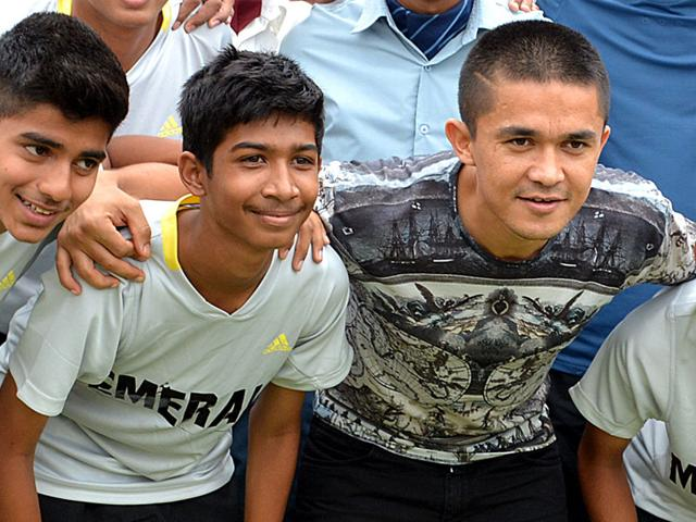 Indian football team captain Sunil Chhetri poses with young players in Indore on Saturday. (Shankar Mourya/HT)