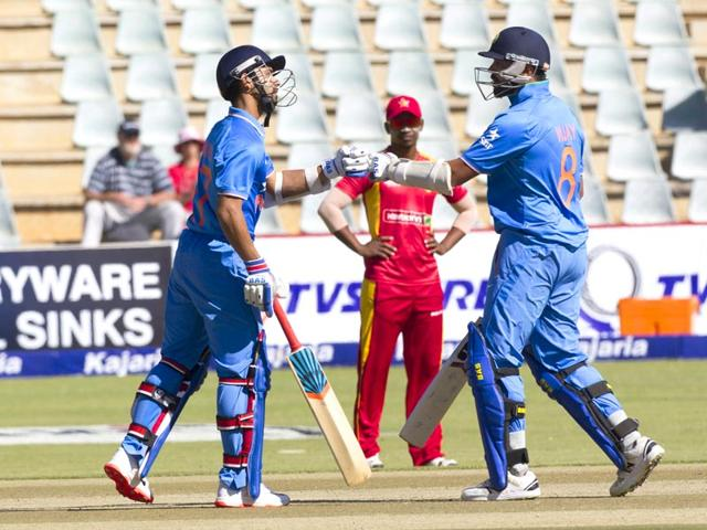 Ajinkya Rahane (L) and Murali Vijay touch gloves during the second ODI between Zimbabwe and India in Harare on July 12, 2015. (AP Photo)