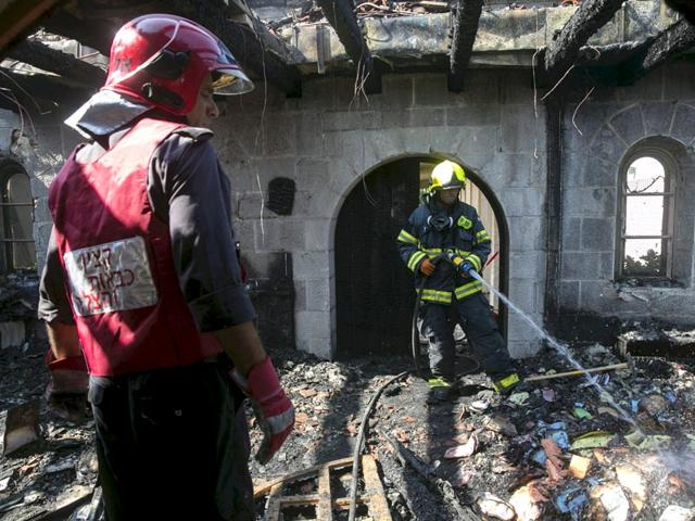 An Israeli fire fighter hoses down burnt leaflets in the Church of Loaves and Fishes,Israeli police on Sunday said that several suspects were arrested over arson attacks on the church. (Reuters Photo)