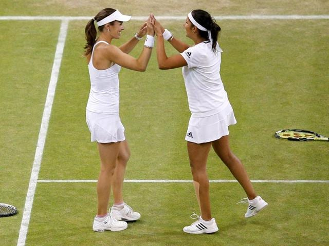 Switzerland's Martina Hingis (R) and India's Sania Mirza (L) celebrate after beating Russia's Ekaterina Makarova and Elena Vesnina in the women's doubles final on day twelve of the 2015 Wimbledon Championships at The All England Tennis Club in Wimbledon, southwest London. Hingis and Mirza won 5-7, 7-6, 7-5. (AFP Photo)