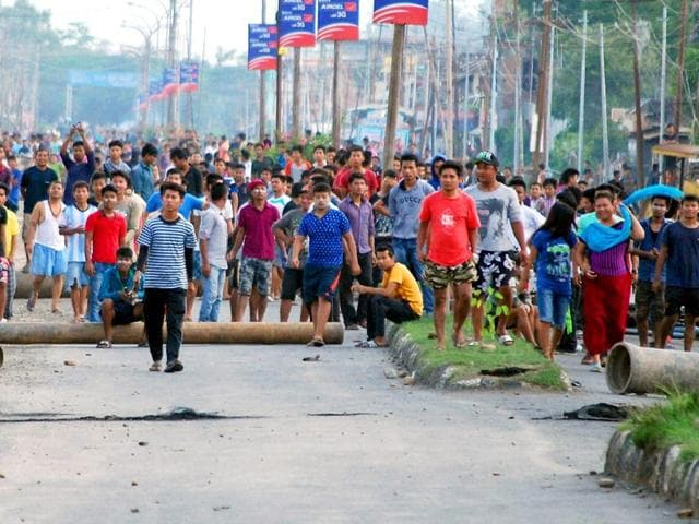 People protest against alleged police atrocities in Imphal on Saturday. The city has been under curfew since wednesday when a class 11 student died in clashes between students and the police. (PTI Photo)