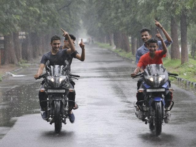 Youngsters enjoying the rainy weather in gehri- route in sector 10, Chandigarh on Saturday (Gurpreet Singh/HT)