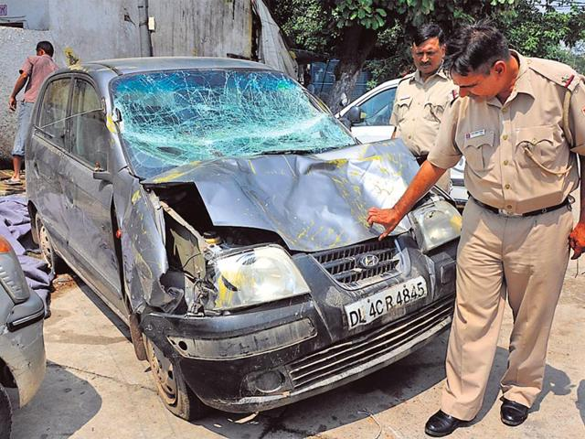 A police officer looks at the damaged car that rammed a barricade in Civil Lines, injuring five policemen. (Sonu Mehta/HT photo)