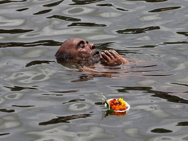 A devotee take a holy dip in Ram Kund on the eve of the flag-hoisting of Kumbh Mela in Nashik. (Arijit Sen/HT photo)