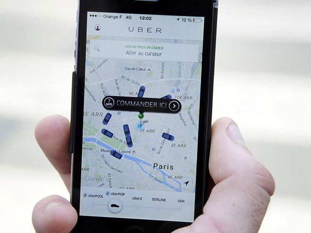 A person using the French version of the Uber app to order a UberPop cab in Paris. Photo: AFP