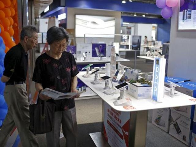 Customers look at mobile phones on display at an electronics market in Shanghai. Photo: Reuters