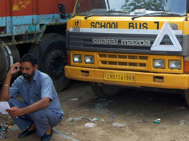 Drunken bus driver Jaswinder Singh sitting in front of the bus, looking at the challan issued by traffic police cop at Balongi Barrier in SAS Nagar on Tuesday, July 14, 2015. (HT Photo)