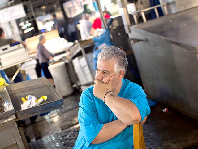 A shopkeeper waits for customers at a fishing market in central Athens, Wednesday, July 15, 2015. Greece's Parliament votes Wednesday on an 85-billion-euro bailout deal meant to prevent the country's economy from collapsing. (AP Photo)