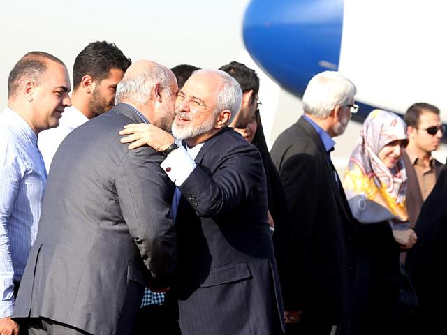 Iranian officials welcome Foreign Minister Mohammad Javad Zarif upon his arrival at Tehran's Mehrabad Airport on wednesday, after Iran's nuclear negotiating team struck a deal with world powers in Vienna. (AFP Photo)