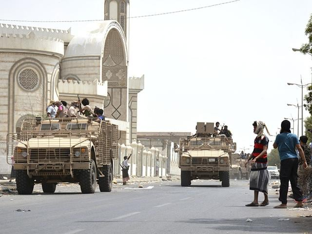 People watch fighters against Shiite rebels as they ride military vehicles on a street in the port city of Aden on Tuesday. Yemeni forces battling the Shiite rebel known as Houthis in the country's south said they took control on Tuesday of the airport in the strategic port city of Aden, driving the rebels there into a part of the city jutting out into the sea. (AP Photo/Abo Muhammed)
