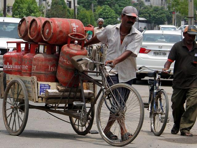 A delivery man carrying LPG cylinders at Kitchlu Nagar in Ludhiana on Wednesday. (JS Grewal/ HT)