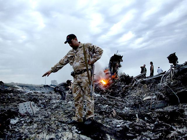A file photo of people walking on the debris at the crash site of the passenger plane in Ukraine.