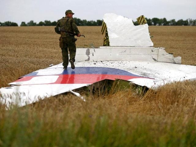 An armed pro-Russian separatist stands on part of the wreckage of the Malaysia Airlines Boeing 777 plane after it crashed near the settlement of Grabovo in the Donetsk region, in this July 17, 2014 file picture. REUTERS
