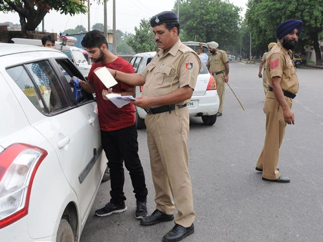 Cops checking the vehicle during a naka at Sector 52 in Chandigarh on Thursday. (Gurminder Singh /HT)