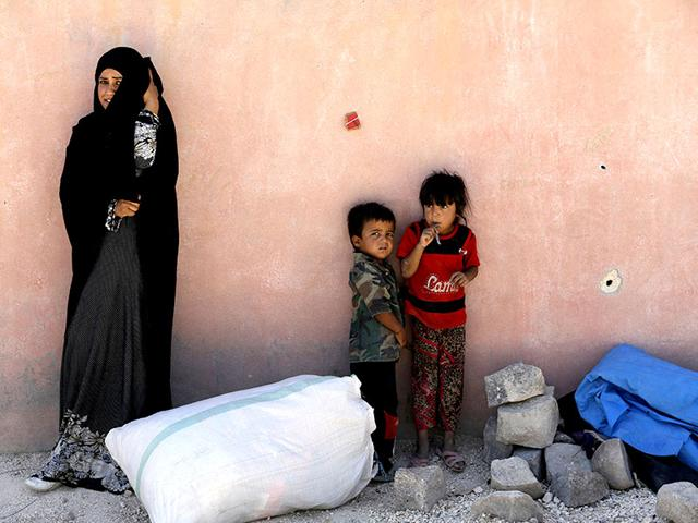 A refugee from the northern Syrian town of Tel Abyad and her children wait while spending the day in Akcakale, Turkey, in this June 18, 2015 file picture. (Reuters)