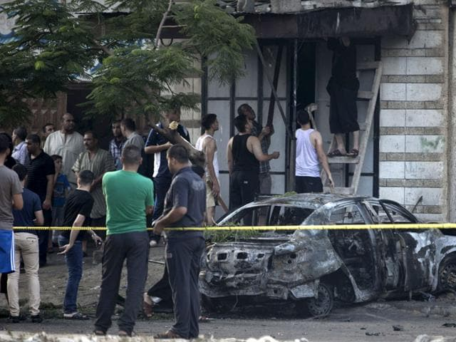 Palestinians gather around a burnt-out car in Gaza after explosions destroyed five cars belonging to members of Hamas and Islamic Jihad. (AFP Photo)