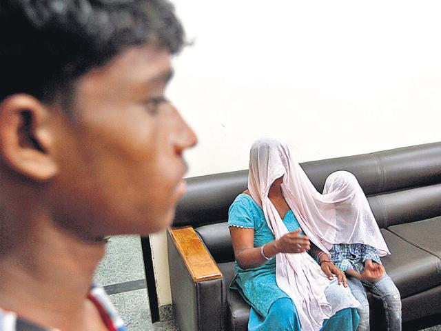 The seven-year-old child with his mother at the Begumpur police station. (Virendra Singh Gosain/HT Photo)