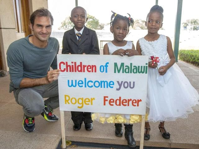 Swiss tennis star Rodger Federer poses with Malawian children at Kamuzu International Airport on his arrival for a visit to Malawi, July 19, 2015. Rodger Federer will on Monday officially launch the Lundu Community Based Childcare Centre in the area of Chief Chitukula in Malawi's Capital City District of Lilongwe.