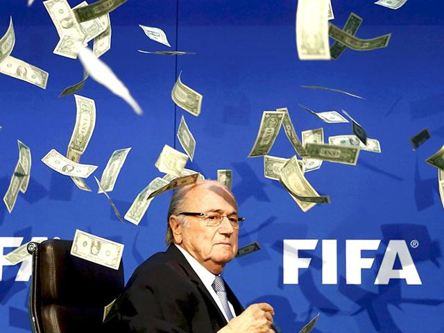 British comedian Lee Nelson (unseen) throws fake money bills at FIFA president Sepp Blatter at a news conference in Zurich on July 20, 2015. (Reuters Photo)