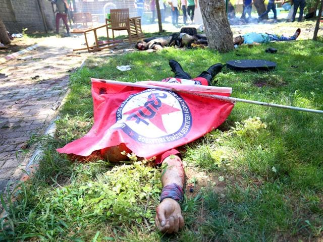 Bodies lie on the ground with one being covered with a Federation of the Socialist Youth Associations flag, after an explosion, in the southeastern Turkish city of Suruc near the Syrian border, Turkey. (AP Photo)