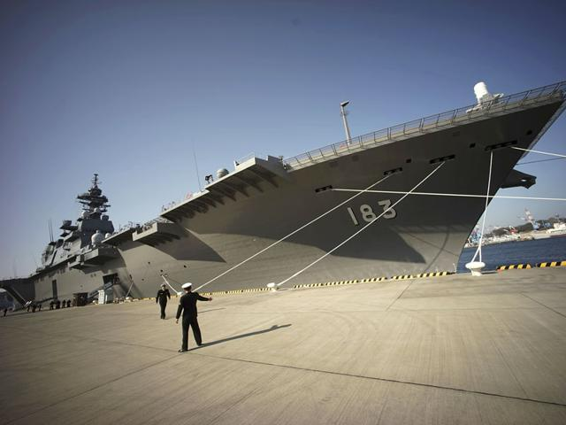 Defence personnel prepare to receive India's defence minister Manohar Parrikar in front of the latest destroyer Izumo of Japan's Maritime Self-Defence Force (JMSDF) in Yokosuka, south of Tokyo. Japan emphasized China as a threat in escalating regional tensions in this year's annual defence report, approved by the Cabinet. (AP File Photo)