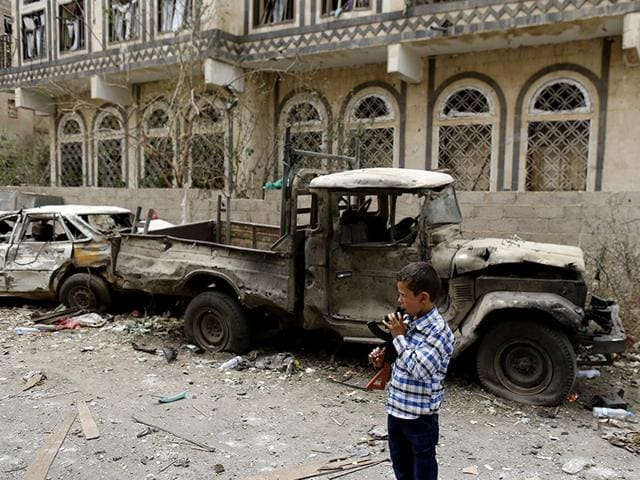 A boy holding a toy rifle stands at the site of a car bomb attack in Sanaa July 21, 2015. A UN aid ship arrived in Aden after four months carrying some much needed relief supplies. (Reuters Photo)