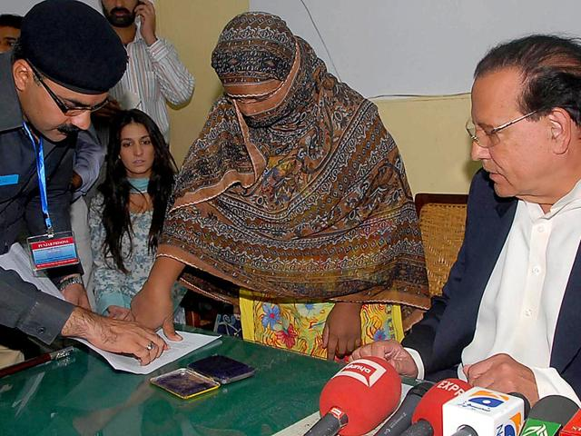 A file photograph shows Pakistani Punjab governor Salman Taseer (R) looking on as Pakistani Christian mother Asia Bibi (C) places a thumb impression on her appeal papers against a death sentence, after she was sentenced to hang after being found guilty of insulting the Prophet Mohammed. (AFP File Photo)