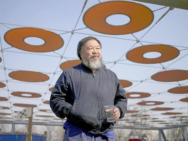 This handout picture released by Chinese dissident artist Ai Weiwei on July 22, 2015 shows Ai Weiwei posing with his passport in Beijing (AFP Photo)