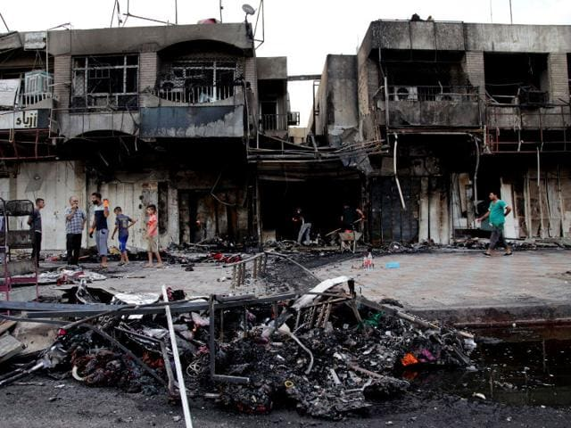 Civilians inspect damages on Wednesday in the eastern neighborhood of New Baghdad after car bomb detonated in front of a busy clothing store on Tuesday killed and injured civilians. (AP Photo/ Khalid Mohammed)