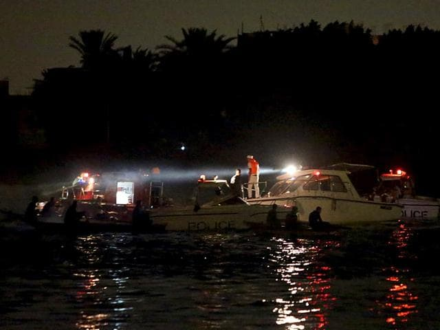 People stand on the bank of the Nile while rescuers search for victims in Cairo. At least 15 people including two children were killed after a cargo boat collided with a ferry on the Nile, hospital, security and political sources said (AFP Photo)