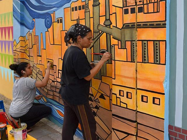 Art teacher Nooryya Shaikh Nabi (R) and her daughter Gaiti Ara give final touches to a design on a wall in the southern port city of Karachi. For years Karachi's walls have been spattered with the bloodstains of murder victims and scrawled with graffiti screeds touting everything from sectarian hatred to quack cures for erectile dysfunction. (AFP Photo/ Asif Hassan)