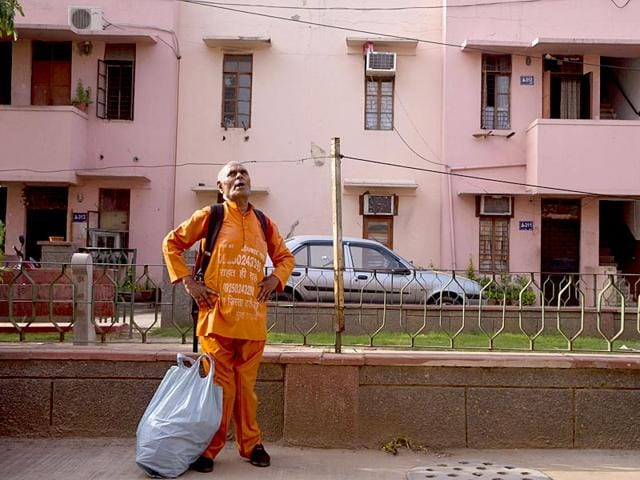 Omkarnath, who goes by the name 'Medicine Baba', calls out to people to donate unused medicines at a government colony in New Delhi. (AP Photo)