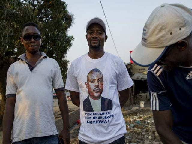 Supporters of President Pierre Nkurunziza, one wearing a t-shirt depicting the president, look on following the announcement of preliminary results in Burundi's presidential elections on July 24, 2015. Nkurunziza won an outright majority in the controversial polls with 69.41% of the vote. (AFP Photo)