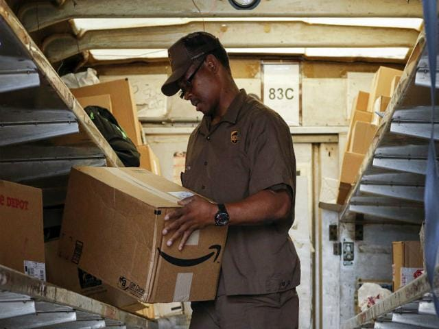 A UPS worker checks an Amazon box to be delivered in New York July 24, 2015. Amazon's shares surged in early trading on Friday, adding more than $46 billion to the company's market value, after strong growth in the cloud business drove a surprise quarterly profit. (Reuters Photo)