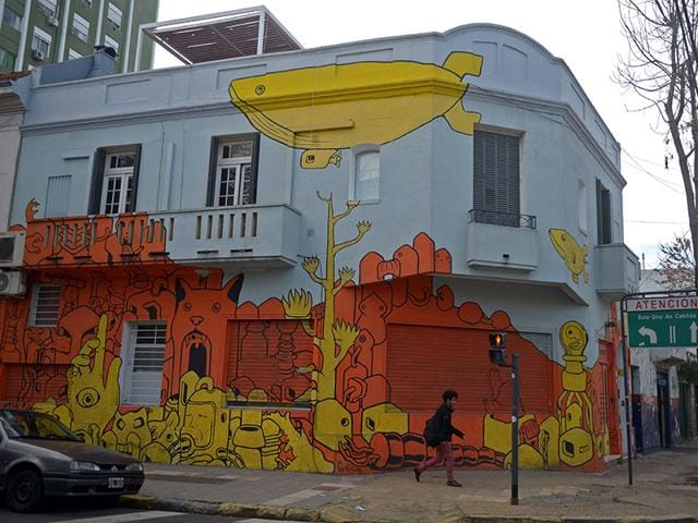 A man walks in front of a house decorated with murals in Buenos Aires on July 1, 2015. (AFP Photi/Eitan Abramovich)
