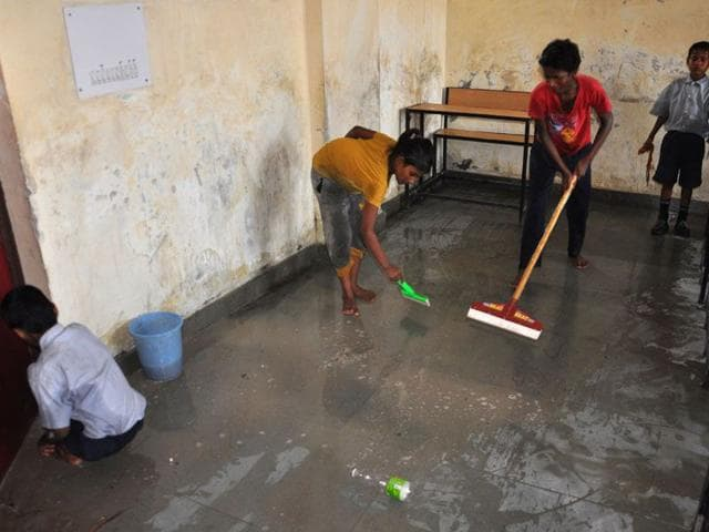 Students cleaning one of the classrooms at Government High School in Hallomajra on Saturday. Karun Sharma/HT