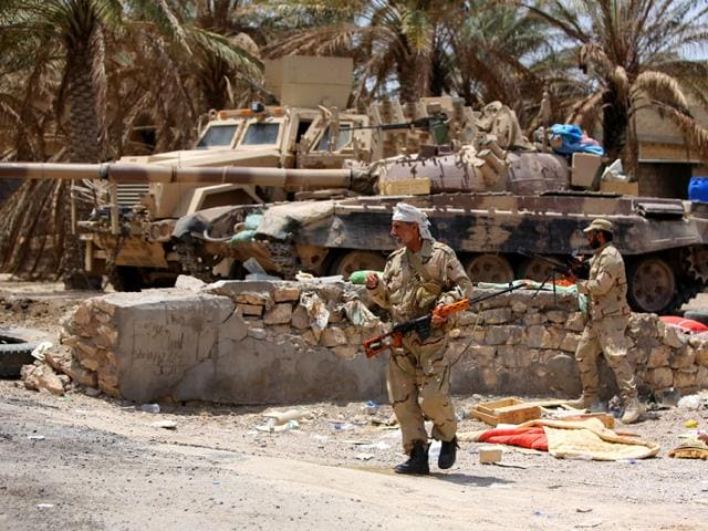 Iraqi Army soldiers with new US-made weapons take combat positions at the front line in an eastern suburb of Ramadi, backed by Shiite and Sunni pro-government fighters (AP Photo)