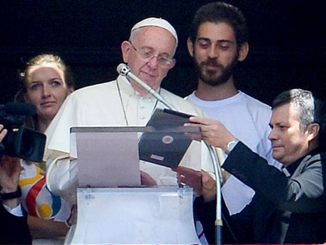 Pope Francis, accompanied by two Polish youths, uses an iPad to register online for the next 2016 World Youth Day in Poland during the Angelus prayer at the Vatican. (AFP Photo)