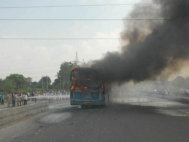Firefighters in action after a Punjab Roadways bus caught fire in Jalandhar on Tuesday. HT Photo