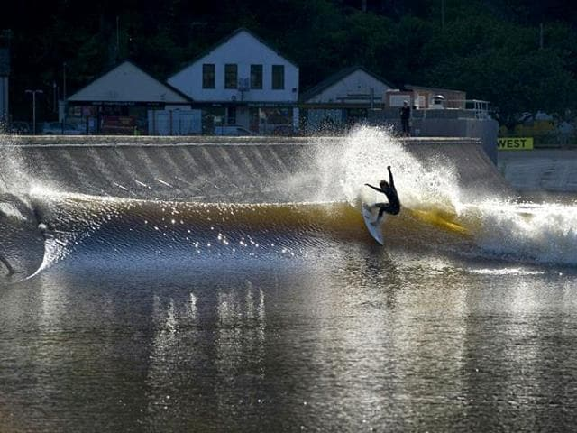A surfer experiences a 300m long and 110m wide artificial lagoon known as Surf Snowdonia in the village of Dolgarrog in north Wales. (AFP Photo)