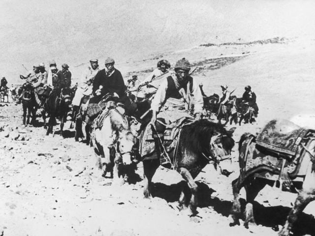 The 14th Dalai Lama fleeing from Tibet to India across the Himalayas, following a failed uprising against the Chinese occupation, in 1959. He is riding a white pony, third from the right. (Getty Images)