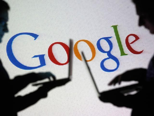 People are silhouetted as they pose with laptops in front of a screen projected with a Google logo. Photo: Reuters