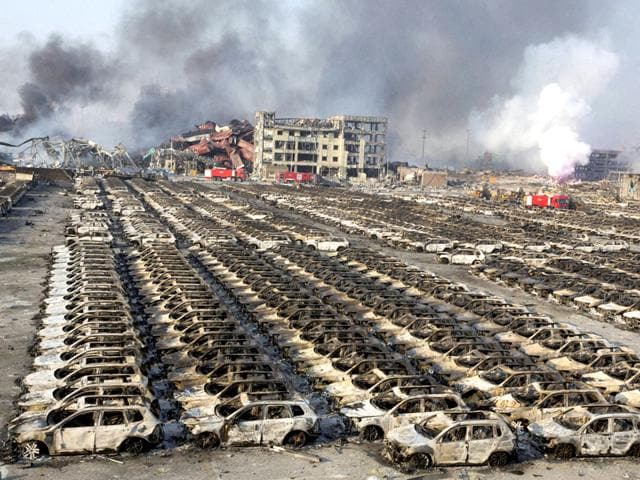 Smoke billows out from the site of an explosion that reduced a parking lot filled with new cars to charred remains at a warehouse in northeastern China's Tianjin municipality. (AP/PTI)