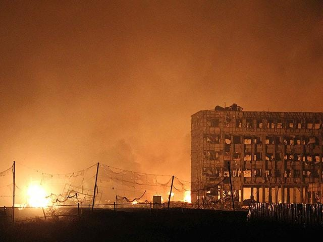 Flames rise next to a damaged building at the site of a series of explosions in Tianjin early on August 13, 2015. A series of massive explosions at a warehouse in the northern Chinese port city of Tianjin killed 17 people, state media reported.(AFP PHOTO)