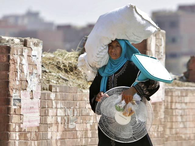 An Egyptian farmer carries an electric fan as she walks through a Cairo street. 76 people have reportedly died due to the heatwave sweeping through the country. (AP Photo)