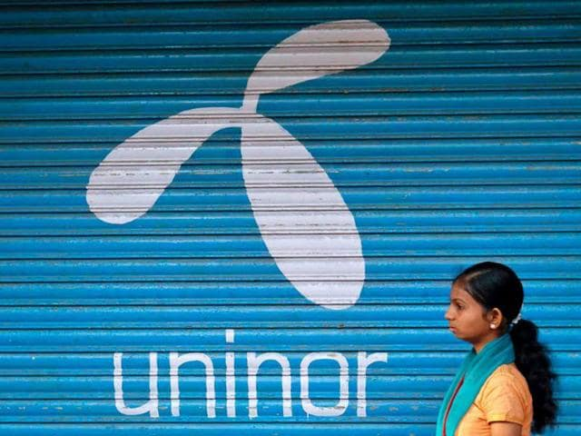 A-girl-walks-past-in-front-of-a-closed-shop-displaying-the-Uninor-logo-on-its-shutter-in-Mumbai-Reuters-Danish-Siddiqui