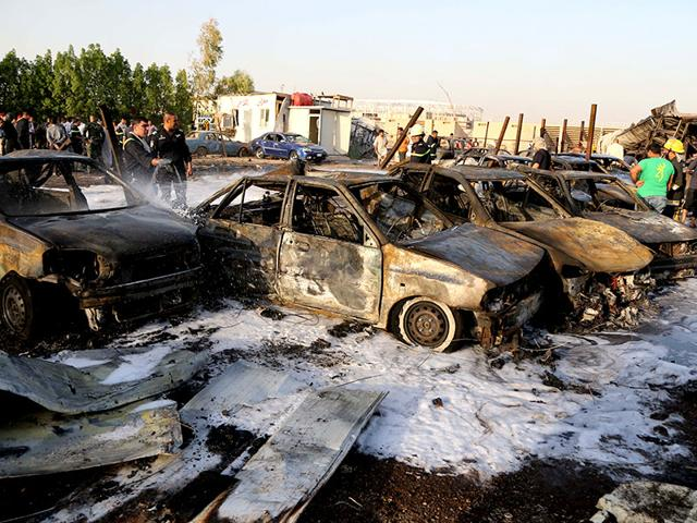 Security forces and civilians gather at the scene of a deadly car bomb in the Habibiya neighborhood of Sadr City, Baghdad, Iraq. (AP Photo)