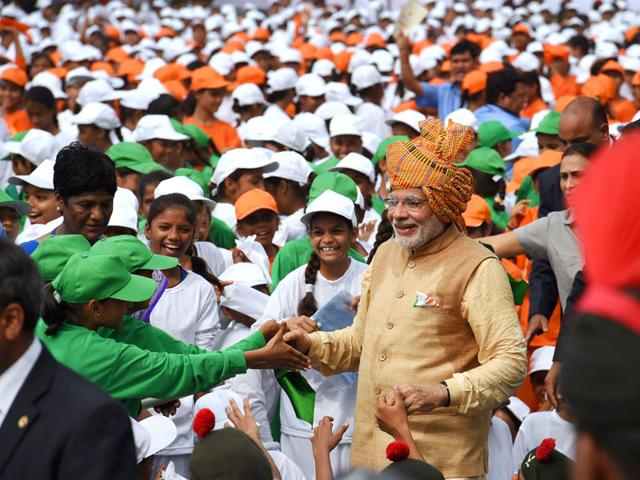 Prime Minister Narendra Modi is greeted as he walks among schoolchildren. In his speech, Modi sought to silence growing doubts about his leadership after key reforms stalled in a rancorous parliament session dogged by allegations of corruption involving some of his top lieutenants. (AFP Photo)